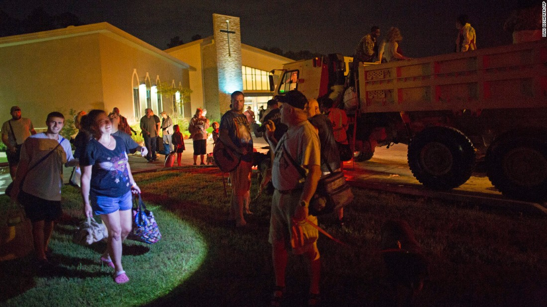 Those displaced by the flooding wait to board National Guard trucks at a Denham Springs church on August 14.
