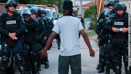 A man talks to police in riot gear in Milwaukee on Aug. 15.