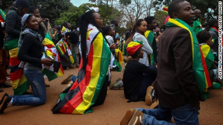 "Supporters of ""ThisFlag campaign"" kneel for prayer at the entrance of the Harare magistrate's court where pastor Evan Mawarire appeared on charges of inciting public violence following his arrest ahead of a planned mass job stayaway on July 13, 2016.  The pastor leading Zimbabwe's new protest movement walked free from court on July 13, 2016 after charges against him of attempting to overthrow President Robert Mugabe's authoritarian government were thrown out.  / AFP / Jekesai Njikizana        (Photo credit should read JEKESAI NJIKIZANA/AFP/Getty Images)"