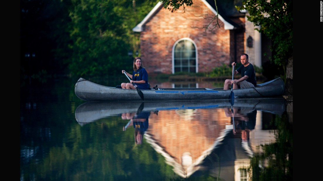 Danny and Alys Messenger canoe away from their flooded home in Prairieville on August 16.