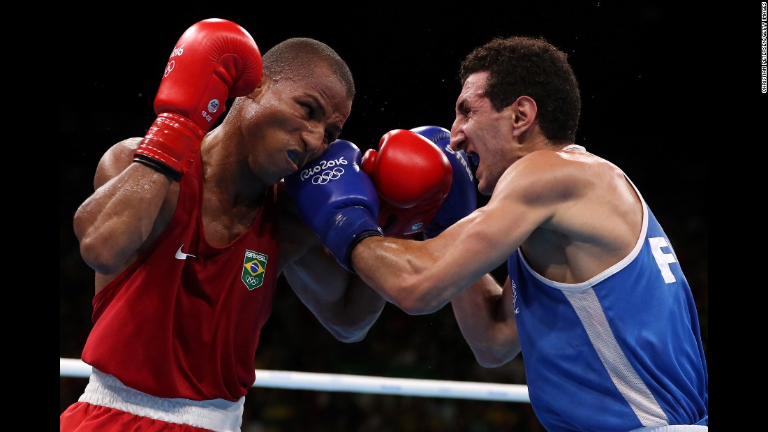 Brazil's Robson Conceicao, left, boxes France's Sofiane Oumiha in the lightweight final. Conceicao won the bout to earn the host country its first-ever gold medal in boxing.