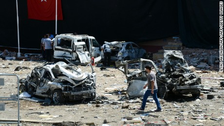 TOPSHOT - Turkish rescue workers stand by the wreckage of a vehicle as a Turkish police officer  inspects a destroyed car and a man walks among the remains at the blast scene following a car bomb attack on a police station in the eastern Turkish city of Elazig, on August 18, 2016. At least three people were killed and another 120 injured on August 18, 2016 in a car bomb attack on a police headquarters in eastern Turkey, a local security source said. The explosion, blamed by Defence Minister Fikri Isik on the outlawed Kurdistan Workers' Party (PKK), happened in the garden of the four-storey building in Elazig.  / AFP / ILYAS AKENGIN        (Photo credit should read ILYAS AKENGIN/AFP/Getty Images)