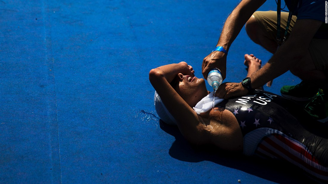 U.S. triathlete Joe Maloy is doused with water after crossing the finish line.