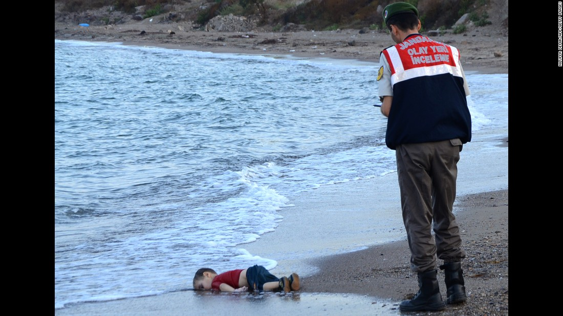 A Turkish police officer stands next to a migrant child's body off the shores of Bodrum, Turkey, on September 2, 2015 after a boat carrying refugees sank on approach to the Greek island of Kos. The picture sent shockwaves across the globe, highlighting the plight of refugees fleeing from war.