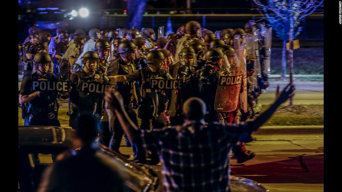 "Police move in on a group of protesters throwing rocks at them in Milwaukee on Sunday, August 14. <a href=""http://www.cnn.com/2016/08/14/us/milwaukee-violence-police-shooting/"" target=""_blank"">Tensions were high</a> as residents gathered to mourn Sylville Smith, an armed man shot to death by police. Protesters torched businesses and threw rocks at officers. Four officers were injured and 17 people were arrested, Mayor Tom Barrett said."