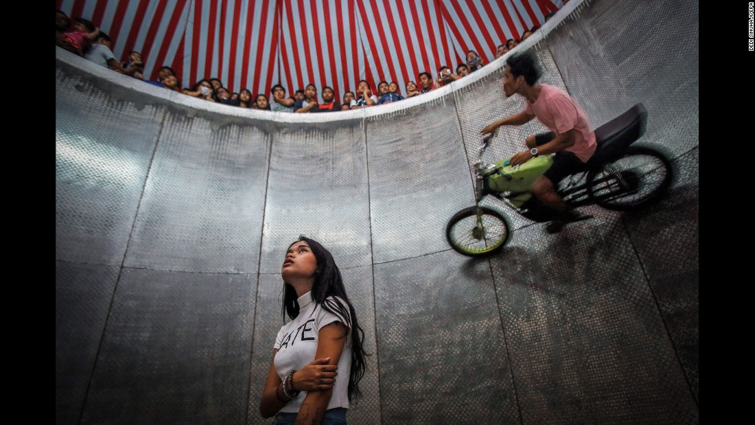 "A young daredevil, center, waits for her turn as another person rides a motorbike around the ""Devil's Barrel"" at a carnival in Deli Serdang, Indonesia, on Saturday, August 13."