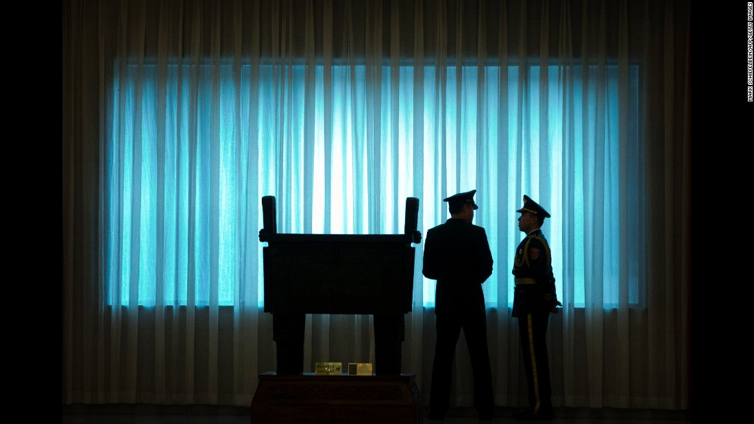 Chinese army officers stand in front of a window Tuesday, August 16, before a welcome ceremony in Beijing for U.S. Army Chief of Staff Mark A. Milley.