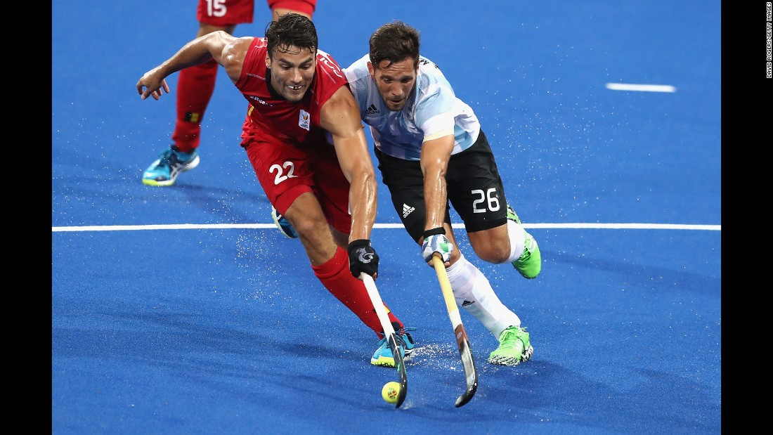 Belgium's Simon Gougnard, left, is challenged by Argentina's Agustin Mazzilli during the field hockey final. Argentina won the gold medal with a 4-2 victory.
