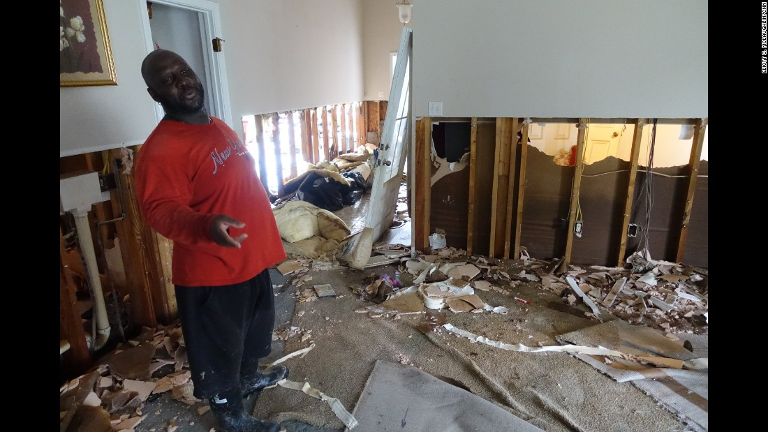 Laytrom Rheams wears muck boots as he works to gut his home of eight years because a quarter-inch of water remained in his carpet almost a week after the historic flooding began. One of his first orders of business: remove the sheet rock so he can treat his home's beams in hopes of combating mold.
