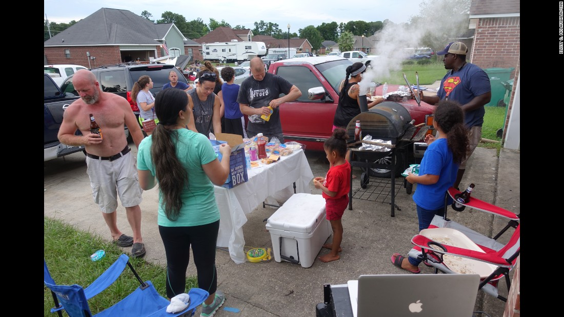 Anthony Williams, at the grill on the right, was lucky. His home sits a couple of feet higher than those of his across-the-street neighbors. It was eerie seeing the destruction, he said, and in a way he felt guilty that his home wasn't inundated as well. On August 18 he held a barbecue, grilling up burgers and dogs for his neighbors. Another fortunate neighbor a few doors down had grilling duties the day before and cooked up a pile of chicken and ribs for everyone.