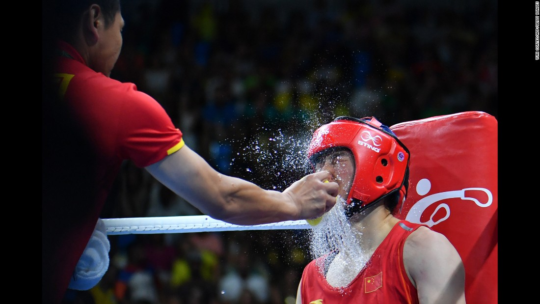 Water is splashed onto Chinese middleweight boxer Li Qian between rounds of her semifinal bout against the Netherlands' Nouchka Fontijn.