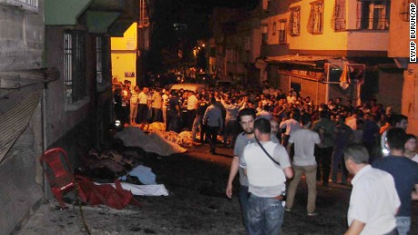 People gather early Sunday at the scene of the explosion in Gaziantep.