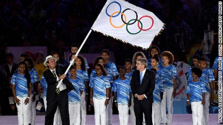RIO DE JANEIRO, BRAZIL - AUGUST 21:  Mayor of Rio de Janeiro Eduardo Paes (L) waves the IOC flag prior to hand to IOC President Thomas Bach (R) on stage at the Flag Handover Ceremony during the Closing Ceremony on Day 16 of the Rio 2016 Olympic Games at Maracana Stadium on August 21, 2016 in Rio de Janeiro, Brazil.  (Photo by Pascal Le Segretain/Getty Images)