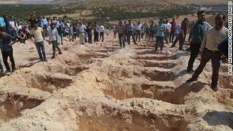 People wait Sunday near freshly dug graves for the victims of the Gaziantep blast.