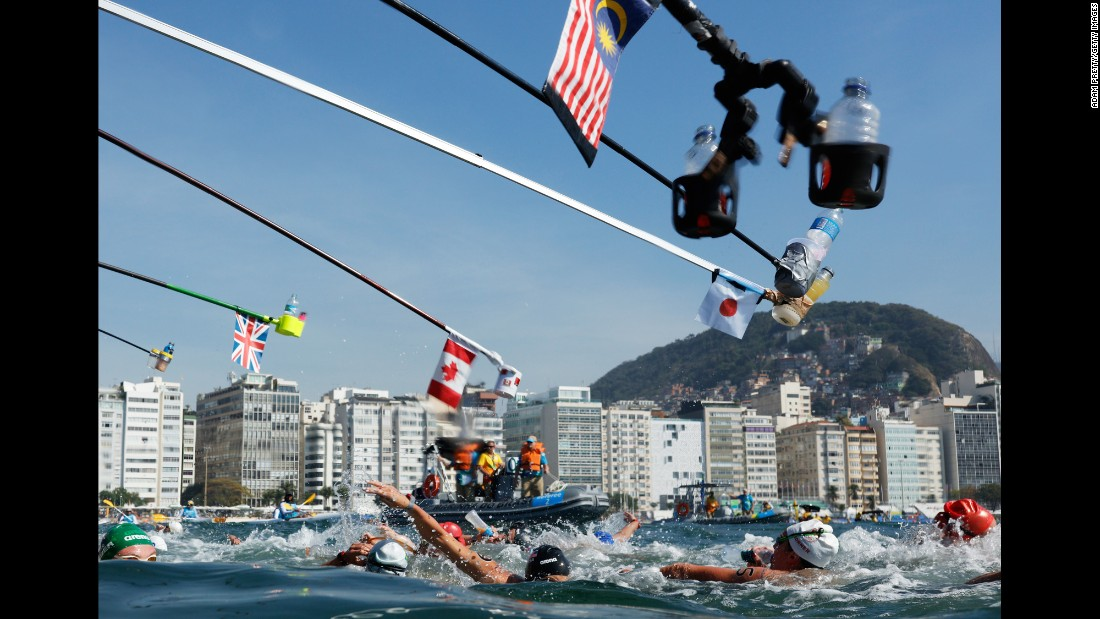 Refreshment bottles are held over women competing in the 10-kilometer open-water swim on Monday, August 15.