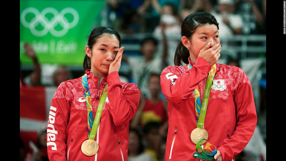 Japan's Misaki Matsutomo, left, and Ayaka Takahashi cry on the podium after winning gold in badminton doubles on Thursday, August 18.