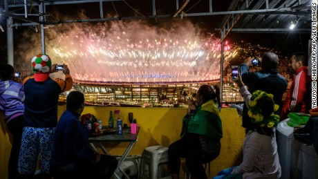 A family watch fireworks of the closing ceremony of Rio 2016 Olympic games over Maracana stadium from Manugeira community (favela) in Rio de Janeiro, Brazil, on August 21, 2016. / AFP / YASUYOSHI CHIBA        (Photo credit should read YASUYOSHI CHIBA/AFP/Getty Images)