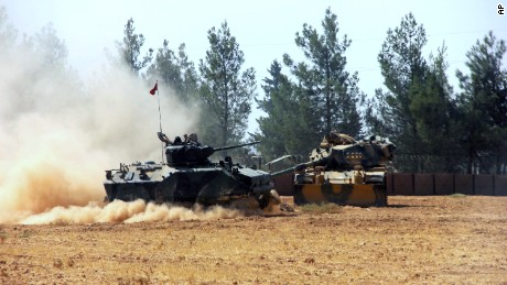 A Turkish army tank and an armored vehicle are in Karkamis, near the Syrian border, on Tuesday.