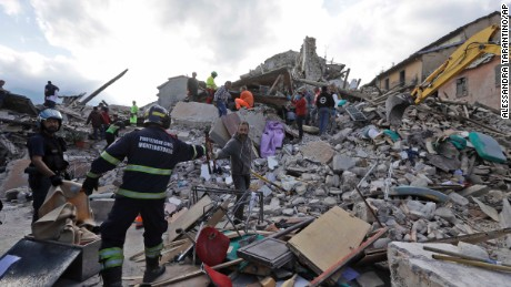 Rescuers search for survivors through the rubble of collapsed buildings on Wednesday in Amatrice, Italy.