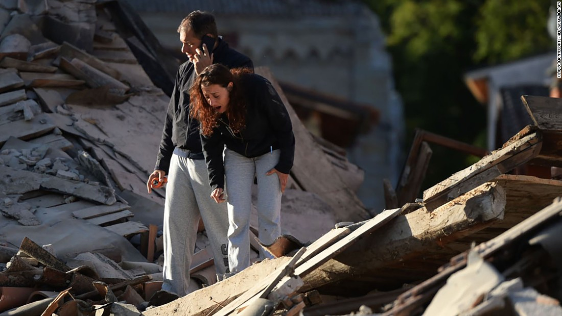 Residents take in the damage in Amatrice.