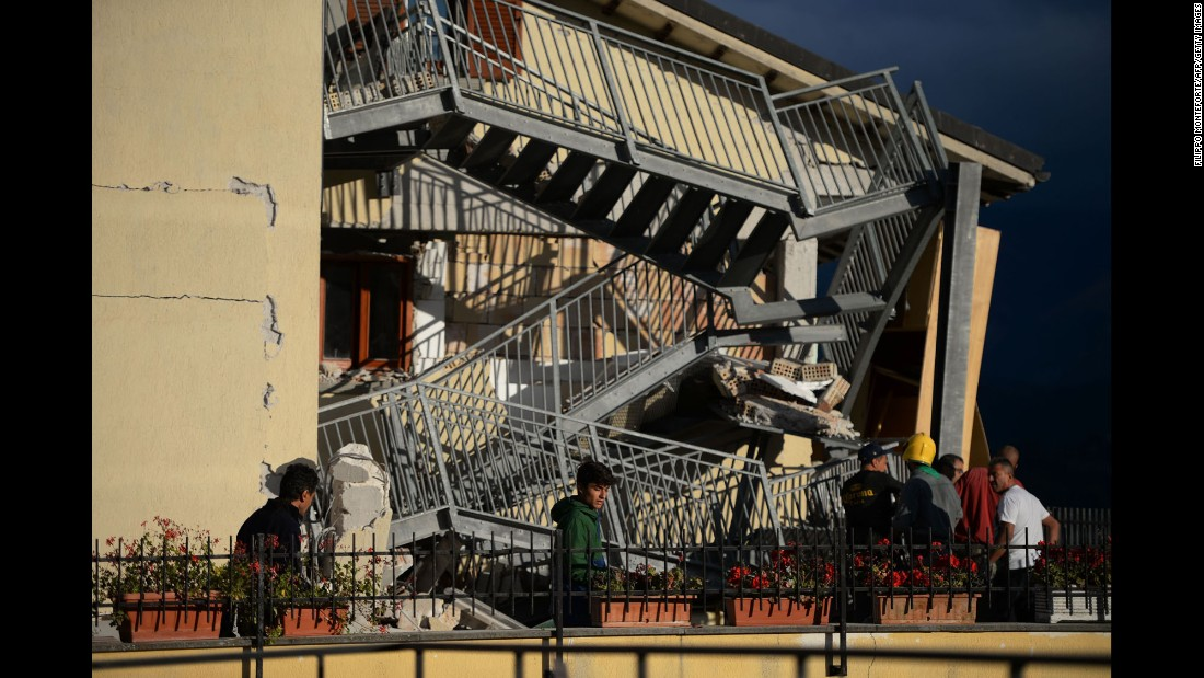 Residents survey a collapsed staircase in Amatrice on August 24.