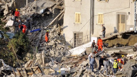 Search and rescue teams survey the rubble of collapsed buildings in Pescara del Tronto.