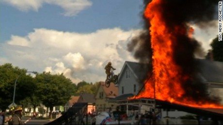 "NY:Daredevil Pastor Jumps Over Helicopter, Wall of Fire    BRIGHTON, N.Y. -- The pastor of a Brighton church who jumped through a wall of fire last month, put it all on the line again Saturday for another stunt.    This time, John ""Mercury"" Morgan launched himself over a helicopter and through fire and flames.    In addition to being a stunt performer, Morgan is a pastor at the Faith on Fire Fellowship. He says his jumps are symbolic of his faith with the ramp representing the highs and lows in life.    The church also gave away book bags and had bounce houses for children"