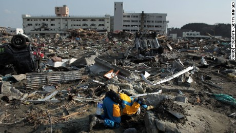 A rescue worker looks under a rock in Minamisanriku, Japan, after an earthquake and tsunami devastated the town.