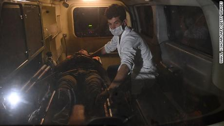 A responder assists an injured man in an ambulance in the aftermath of the university attack.