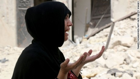 A Syrian woman reacts following a reported  barrel bomb attack on the Bab al-Nairab neighbourhood of the northern Syrian city of Aleppo.