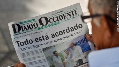 A man reads a newspaper in Cali, Colombia, on August 25, 2016 announcing that the Colombian government and the Revolutionary Armed Forces of Colombia (FARC) guerrillas signed in Havana a historic and definitive agreement to end a half century of armed conflict. Colombia's government and the FARC rebels have reached a historic peace agreement on August 24 to end their half-century civil war that cost hundreds of thousands of lives. After nearly four years of negotiations in Cuba, the two sides announced a final deal Wednesday, which President Juan Manuel Santos said would be put to a decisive referendum on October 2 / AFP PHOTO / LUIS ROBAYOLUIS ROBAYO/AFP/Getty Images