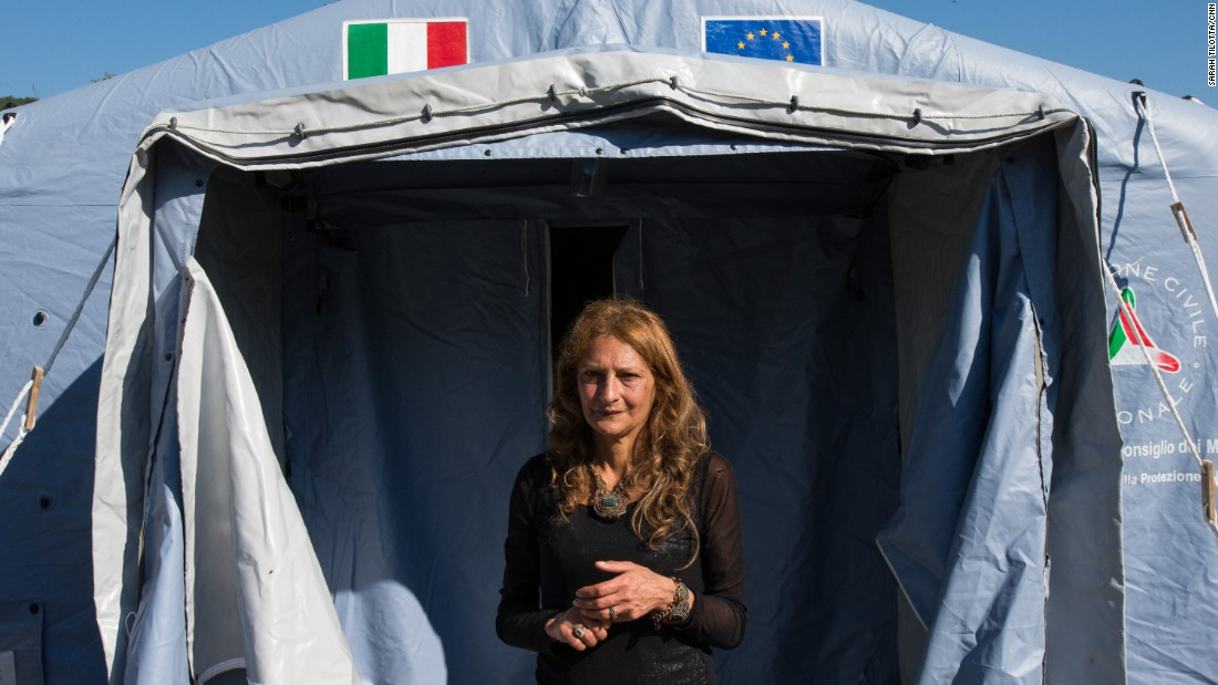 AnnaMaria Volpetti, 52, stands at the entrance of the tent where she and her family have sought refuge after their ancestral holiday home was ruined in Accumoli.