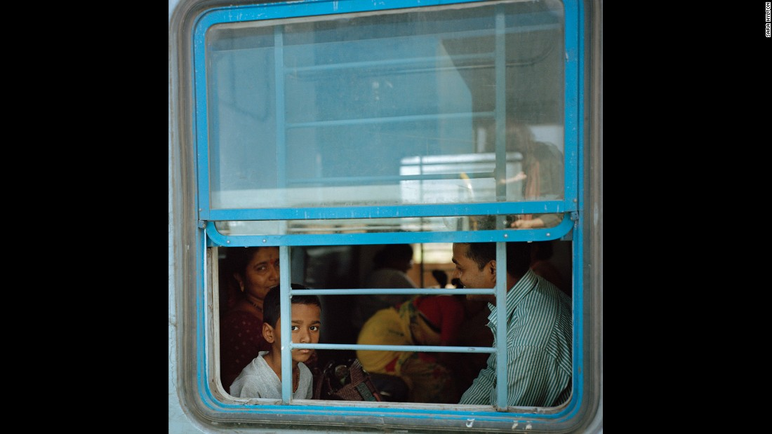 "A boy peers out of a window while his family travels by train in the southern Indian state of Kerala. Photographer Sara Hylton spent months traveling India's vast railway system. She said ""the thing that stands out to me most about Indian trains is their intensity. ... Their scope and their culture is so much more intense than what I experienced on other trains. Everything feels multiplied."""
