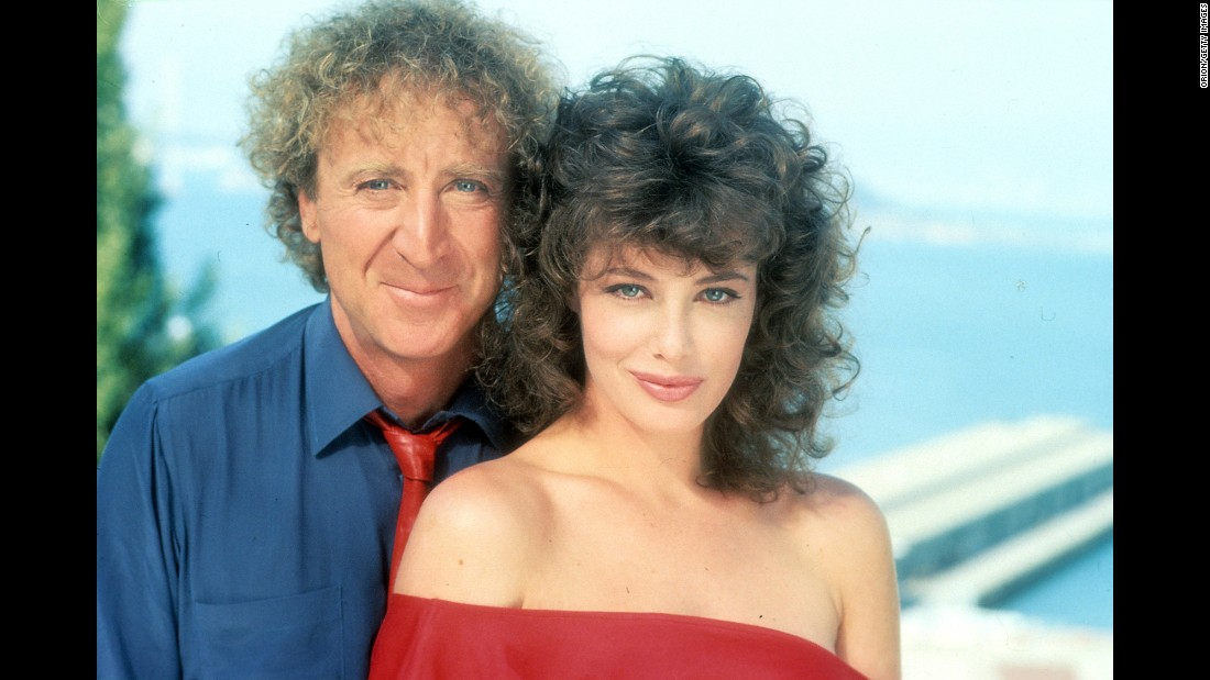 "Wilder poses with actress Kelly LeBrock for a photo promoting the 1984 film ""The Woman in Red."" Wilder also directed."