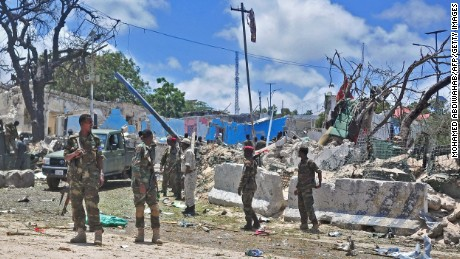 Somali security forces patrol the scene of a suicide car bomb blast Tuesday in Mogadishu.