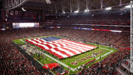 An American flag covers the field during the National Anthem before the NFL game between the Cincinnati Bengals and the Arizona Cardinals  on November 22, 2015.