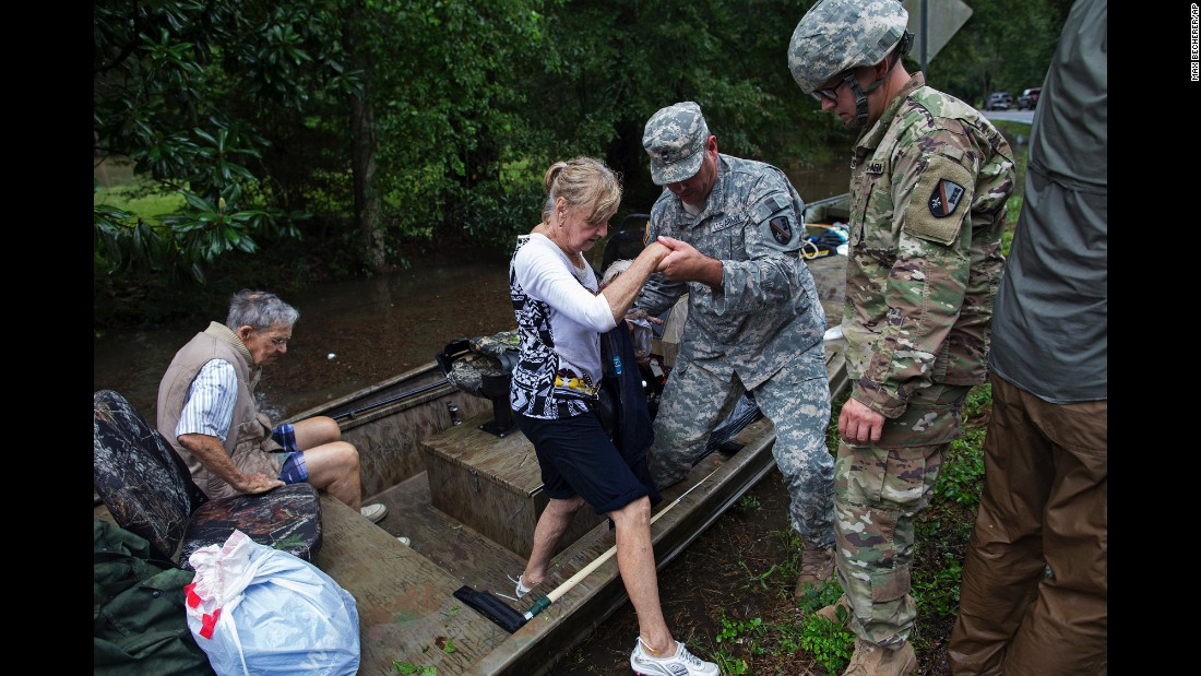 "Members of the Louisiana Army National Guard rescue people from rising floodwaters near Walker, Louisiana, on Sunday, August 14. <a href=""http://www.cnn.com/2016/08/13/us/gallery/louisiana-flooding/index.html"" target=""_blank"">More than 30,000 people had to be rescued</a> in southern Louisiana after heavy rains caused flooding."