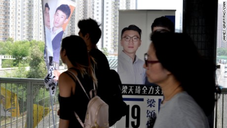 Commuters walk past signs bearing Edward Leung's face in Hong Kong's New Territories East constituency.