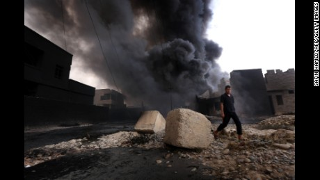 An Iraqi man walks near smoke billowing from oil wells, set ablaze by ISIS before fleeing the oil-producing region of Qayyarah, on August 30, 2016.