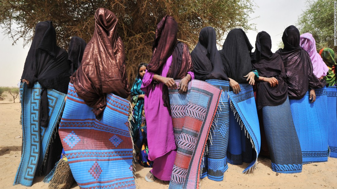 "A traditional ceremony in a village near Abalak, Niger, shows veiled Tuareg women wrapped in rugs to hide their bodies from visitors' looks, according to local custom. Jubber says the Sahel region -- the semiarid belt of land south of the Sahara, to which Abalak belongs -- is the site of what he calls ""the first climate change war,"" where disputes over resources and land rights have made life difficult for nomadic herdsmen."