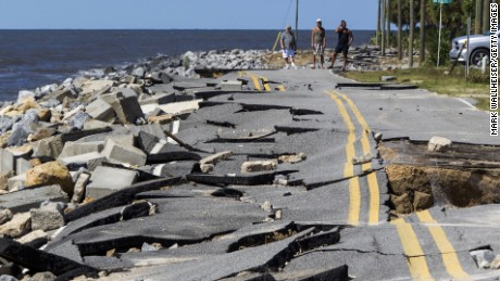 Residents look at Alligator Point road that collapsed during the storm surge from Hurricane Hermine.