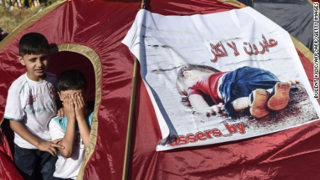 Children sit inside a tent bearing an image of  three-year-old Aylan Kurdi, the Syrian toddler who's body washed up on a beach in Turkey,  as Syrian migrants gather near the highway on the way to the Turkish-Bulgarian border at Edirne on September 15, 2015, in Edirne.  Over half a million migrants have crossed the European Union's border so far this year, up from 280,000 in 2014, the bloc's Frontex border agency said -- but warned some people may have been counted twice.  AFP PHOTO/BULENT KILIC        (Photo credit should read BULENT KILIC/AFP/Getty Images)