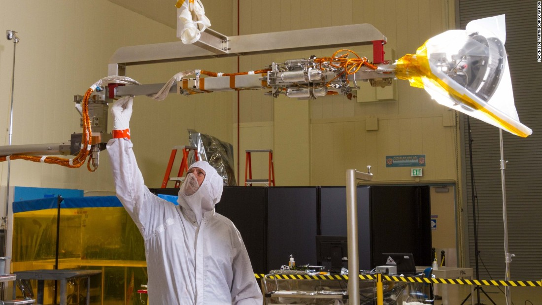 OSIRIS-REx will briefly touch asteroid Bennu to take a sample of the space rock. It will use its 11-foot ( (3.35 meters) robot arm, called the Touch-and-Go Sample Arm Mechanism, or TAGSAM. Above, a worker at Lockheed Martin tests the arm.