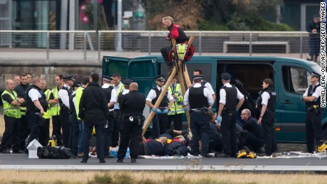 Emergency services surround Black Lives Matter protesters Tuesday on a London City Airport runway.