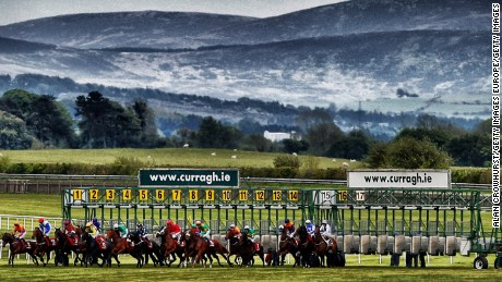 Runners break from the stalls in the back straight  at Curragh race course.
