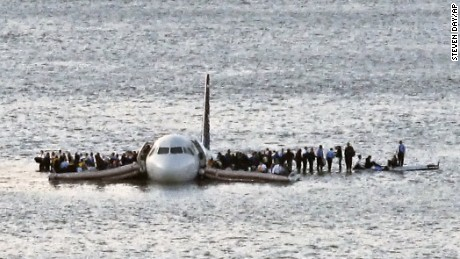 In this January 2009 file photo, airline passengers wait to be rescued on the wings of a US Airways Airbus 320 jetliner that safely ditched in the frigid waters of the Hudson River in New York, after a flock of birds knocked out both its engines.