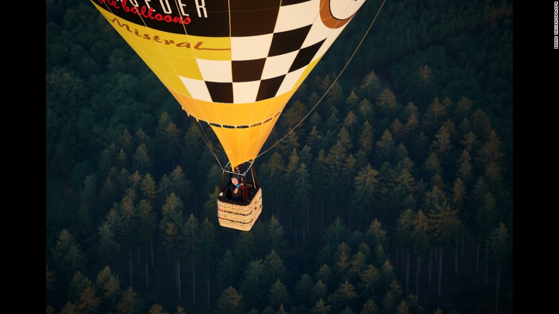 A hot air balloon flies above a forest in Arnsberg, Germany, on Thursday, September 8.