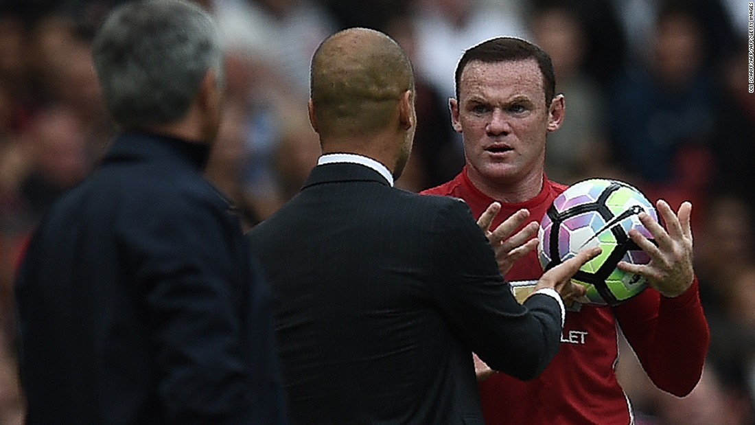 Manchester United's English striker Wayne Rooney (R) and Manchester City's Spanish manager Pep Guardiola clash on the touchline as Rooney tries to retrieve the ball.