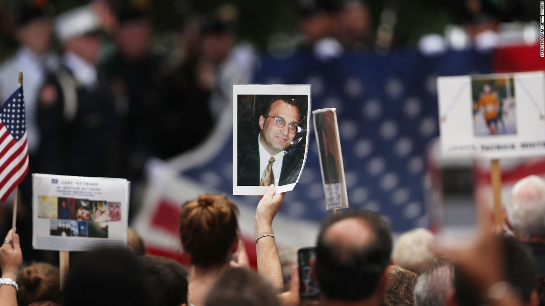 Attendees hold photographs of loved ones lost in the September 11 terrorist attacks at a commemoration ceremony Sunday at the National September 11 Memorial and Museum in New York.