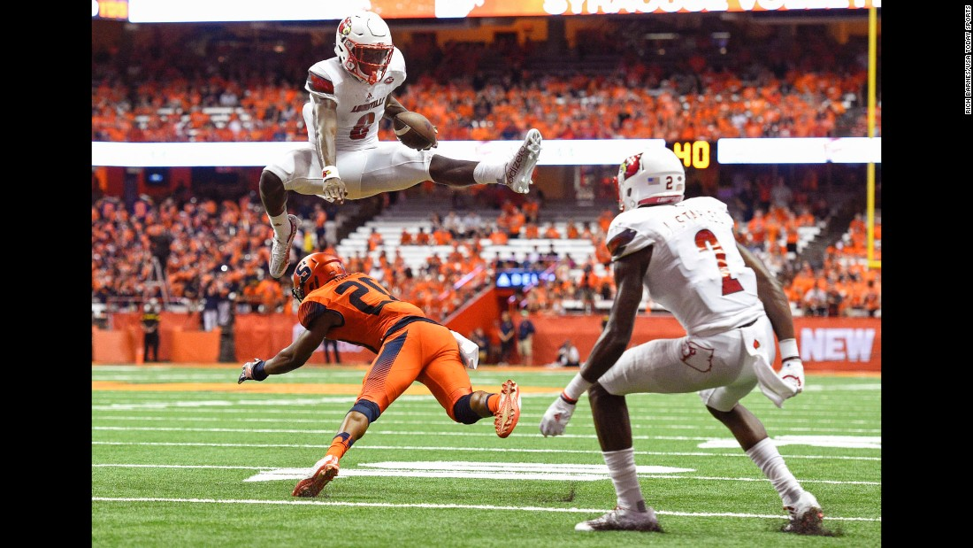 Louisville quarterback Lamar Jackson leaps over Syracuse's Cordell Hudson during the second quarter in Syracuse, New York, on Friday, September 9. Louisville won 62-28.